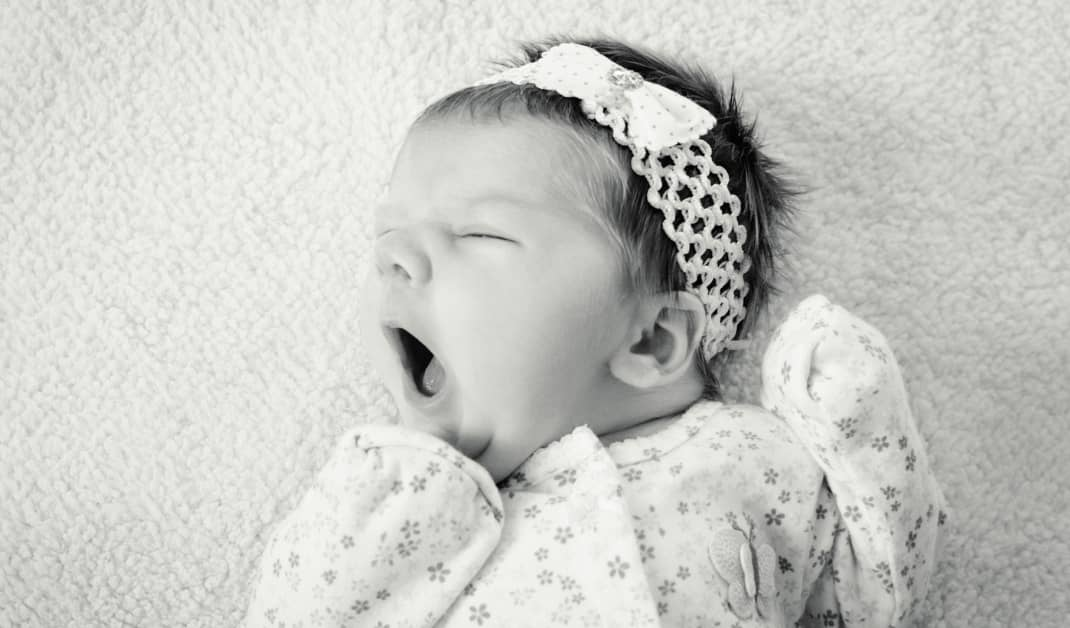 Black and white image of a baby yawning